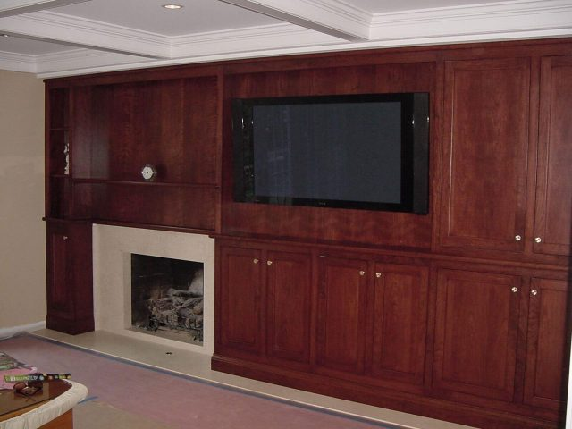 Fireplace surround with cherry wood cabinetry