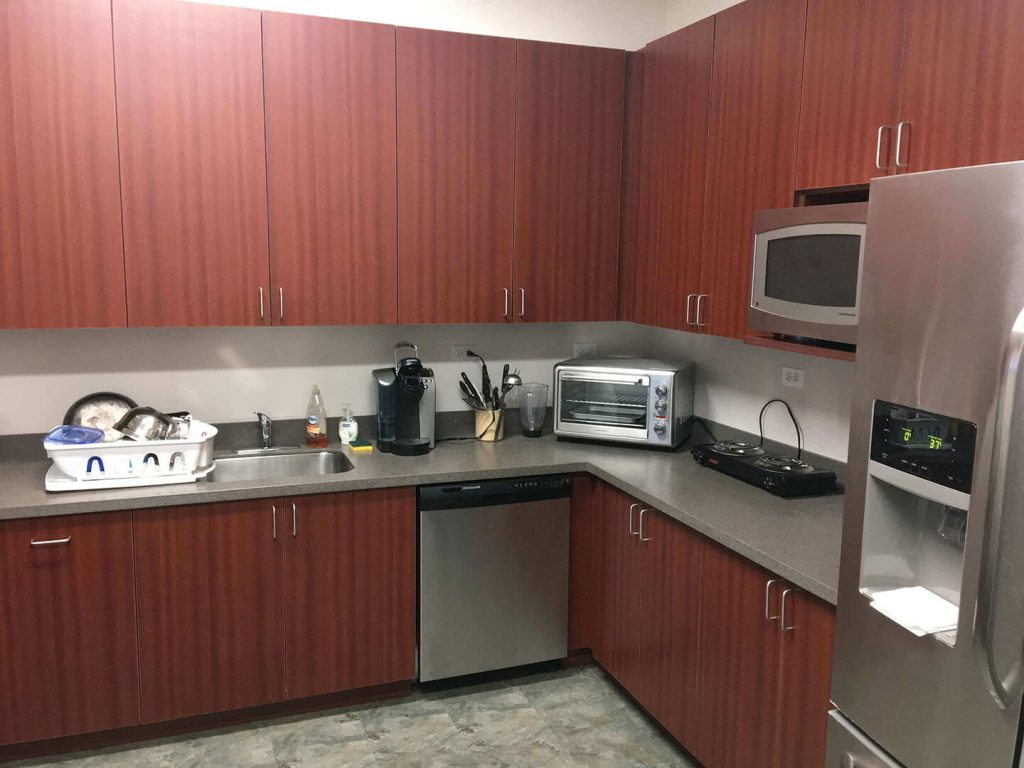 Commercial breakroom with laminate cabinets and solid surface countertop