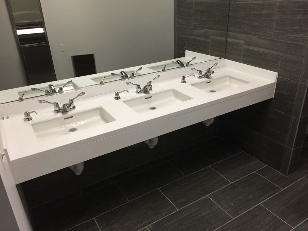 Restroom with white solid surface countertop