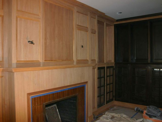 Fireplace surround with unfinished mahogany cabinets