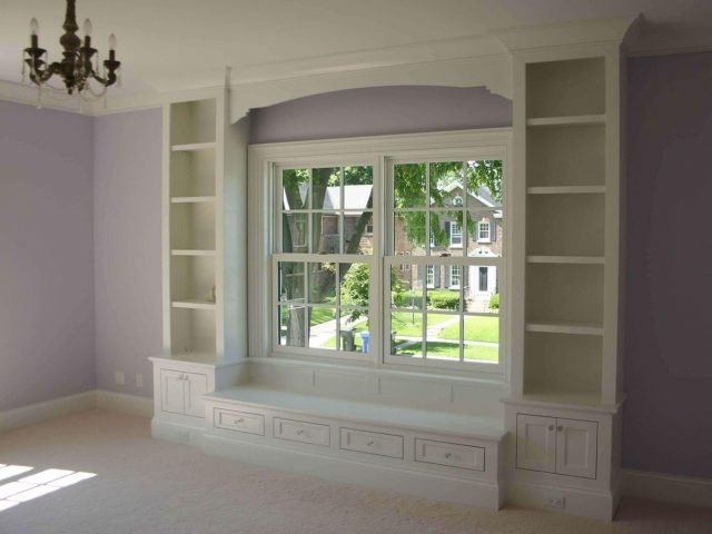 Window seat surround with white bookcases and cabinets